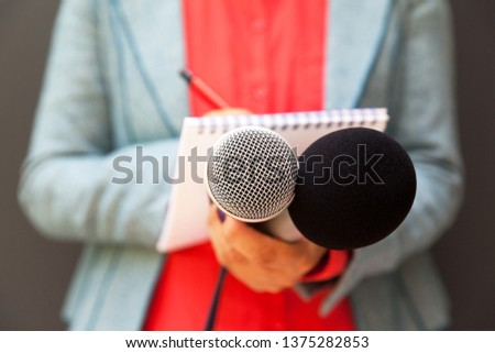 Female reporter at press conference, writing notes, holding microphone