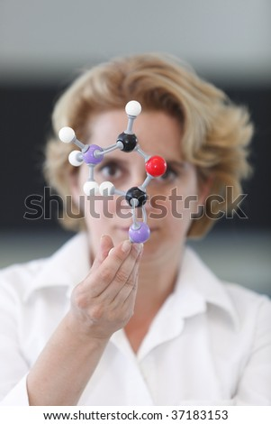 Female researcher analyzing a molecular model in a laboratory.