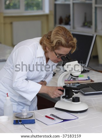 Female researcher looking in a hurry through a microscope in a laboratory.