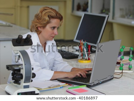 Female researcher working on a laptop at her workplace in a laboratory.All inscriptions are mine.