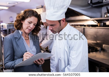 Female restaurant manager writing on clipboard while interacting to head chef in commercial kitchen