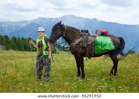 Female rider and horse with saddlebags at mountains