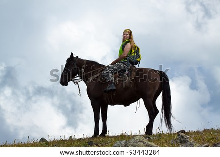 Female rider on horseback against cloudy sky