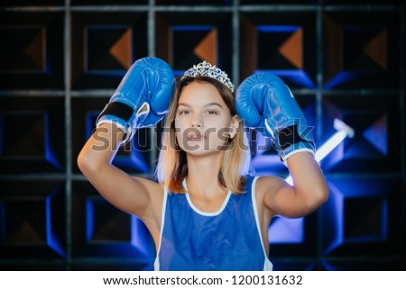 Female rivalry.Woman with gold crown on her head and in a boxing gloves.Sport. Competition. Boxing.  #1200131632