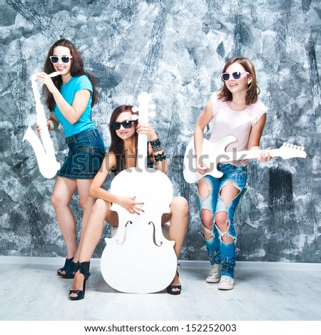 female rock band. girls with musical instruments: cello, sax and guitar