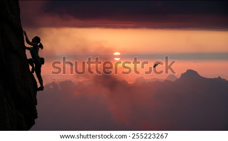 Female rock climber and mountain sunset.\ Silhouette of elegant female extreme climber surrounded by alpine landscape with lake and bright red sunset.