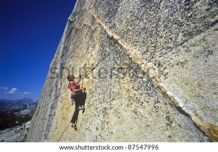 Female rock climber struggles for her next grip on a challenging ascent.