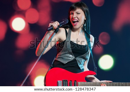 Female rock star with electric guitar singing with a microphone