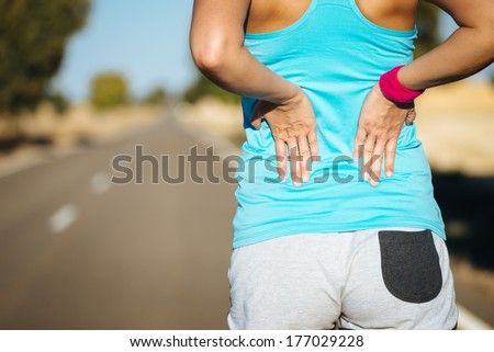 Female runner athlete back injury and pain. Woman suffering from painful lumbago or kidney illness while running in rural road.