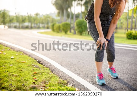 Female runner athlete knee injury and pain. Woman suffering from painful knee while running in the park.