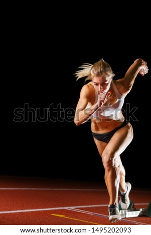 Female runner athlete starting running sprint race on the lane. track and field athletic concept image isolated on black with copy space