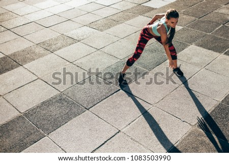 Female runner doing stretching workout. Woman warming up outdoors. #1083503990