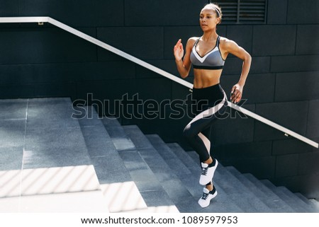 Female runner exercising on staircase, doing outdoor workout #1089597953