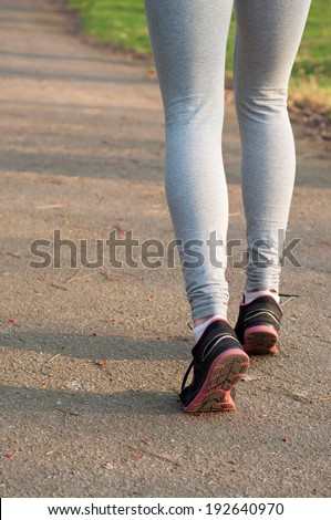 Female runner feet running on the road outdoors at nature. Closeup, main focus on the shoe. On a bright sunny spring day