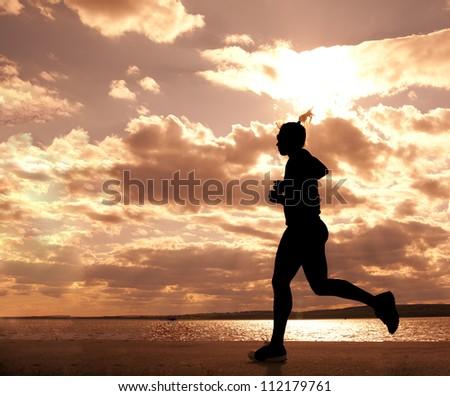 Female runner full length silhouette against the blue sky and sun