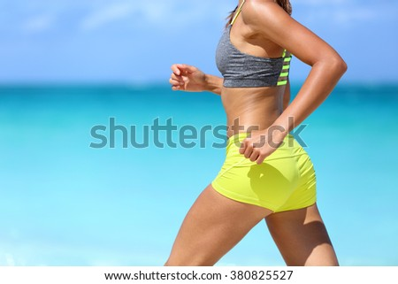 Female runner on beach with sports bra and shorts. Midsection closeup of body of a woman athlete running with speed fast training cardio wearing neon yellow activewear outfit. Active lifestyle.