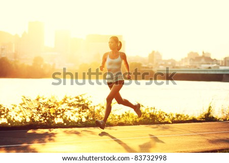 female runner running at sunset in city park. Healthy fitness woman jogging outdoors. Montreal skyline in background.