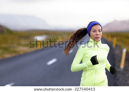 Female runner running in warm clothing for winter and autumn outside. Woman runner training in cold weather living healthy active lifestyle.