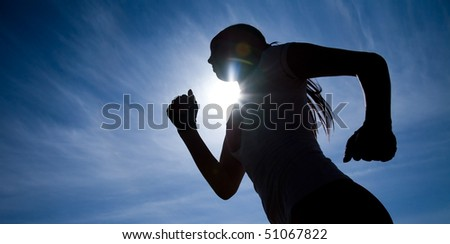 Female runner silhouette against the blue sky and sun