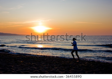 Female runner silhouette  with a soft pastel sunset sky and sea as backdrop