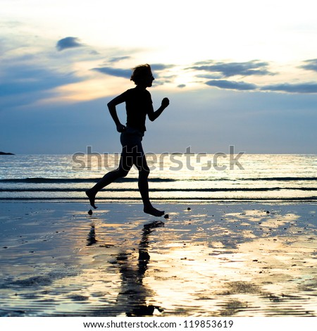 Female runner silhouette with a soft pastel sunset sky as backdrop (backlit)