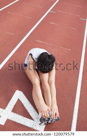 Female runner stretching legs on running track