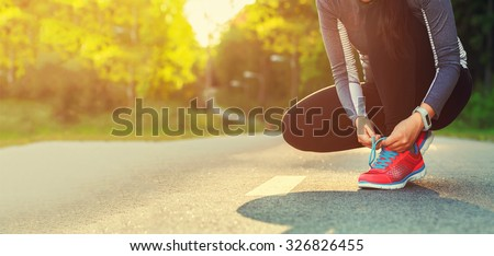Female runner tying her shoes preparing for a run a jog outside
