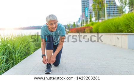 Female runner tying her shoes preparing for a run a jog outside. Close up of young woman tying her laces before a run. A fit and active woman tying her shoes before jogging in a park.