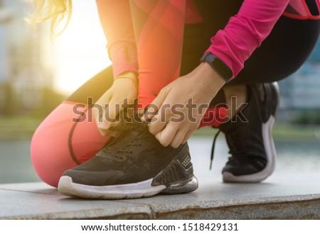 Female runner tying her shoes preparing for a run jog outside