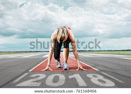 Female runner waits for her start at an airport runway. In the foreground the painted date 2018 symbolises the start into the new year. #761568406