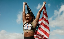 Female runner with a medal celebrating victory holding american flag over her head. Happy american athlete holding the US flag looking away and screaming.