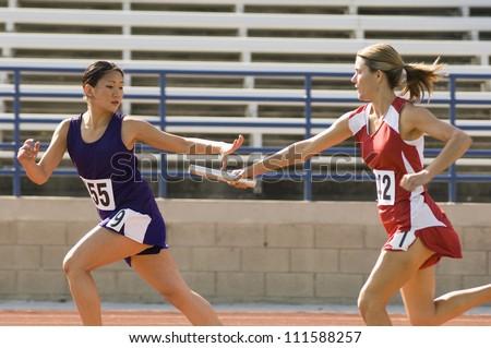 Stock Photo Female runners passing baton in relay race