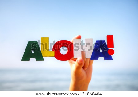 Female's hand holding colorful word 'Aloha' against blue background