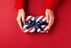 Female's hands in red pullover holding striped gift box with blue ribbon on red background. Christmas, New Year, Valentine's day and birthday concept.