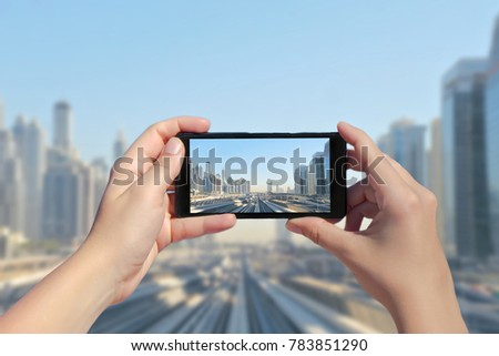 Female's hands take a picture of Dubai monorail and skyscrapers on mobile phone. Picture of subway road on downtown city Dubai on smartphone. United Arab Emirates