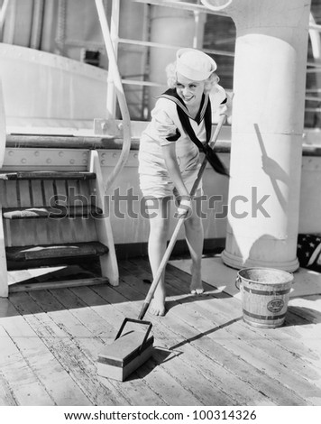 Female sailor swabbing boat deck