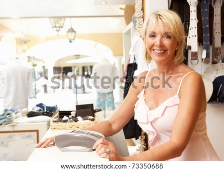 Female Sales Assistant At Checkout Of Clothing Store