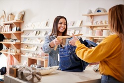 Female Sales Assistant In Independent Clothing And Gift Store Serving Female Customer