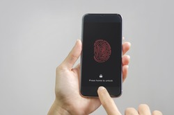 Female scanning fingerprint on smartphone, on gray background. Unlock mobile phone.