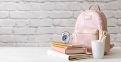 Female school backpack with stationery supplies on desk at white loft brick background. Elegant bag for carrying schooler accessories with notebook, pencil and sketchbook. Back to school concept