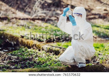 female scientist examining the liquid contents of flask in the forest. Ecology and environmental pollution concept.