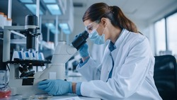 Female Scientist in Face Mask and Glasses Looking a Petri Dish with Genetically Modified Sample Chemicals Under a Microscope. Microbiologist Working in Modern Laboratory with Technological Equipment.