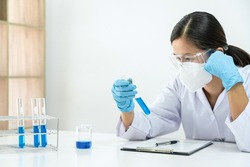 Female scientist in medical mask is working to research and experiment a chemical in laboratory while looking a blue liquid on test tube and writing about summary of experimental results on clipboard