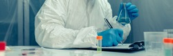 Female scientist with bacteriological protection suit investigating in the laboratory