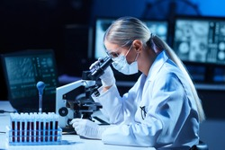 Female scientist working in modern lab. Doctor making microbiology research. Laboratory tools: microscope, test tubes, equipment. Coronavirus covid-19, bacteriology, virology, dna and health care.