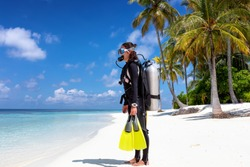 Female scuba diver in full equipment stands on a tropical beach ready to enter the water