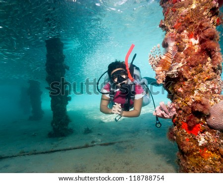 Female SCUBA diver next to a Lionfish underneath a manmade jetty