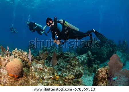 Female SCUBA diver on a tropical coral reef #678369313