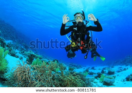 Female Scuba Diver swimming over a coral reef signals that she is Okay #80811781