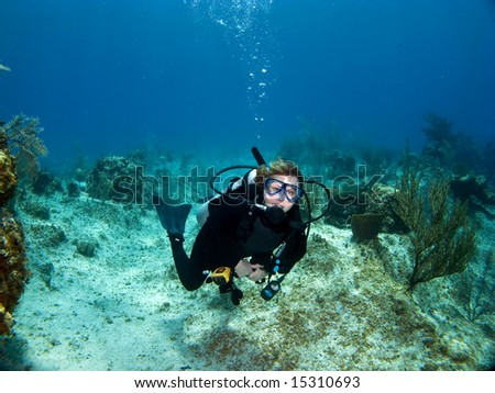 Female Scuba Diver swimming while looking at the Camera